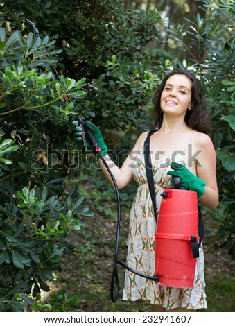 Young woman in dress spraying tree plant in orchard - stock photo