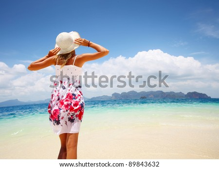 Young woman in dress standing on a beach and looking to a sea. Distorted horizon - stock photo