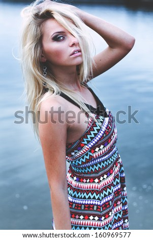 Young woman in dress walking alone on the beach - stock photo
