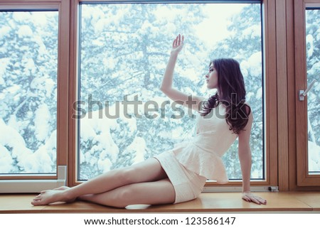 young woman in elegant short dress barefoot sit by window looking at winter snow day - stock photo