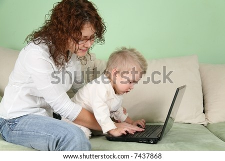 young woman in eyeglasses with notebook and child on sofa - stock photo