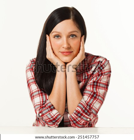 Young woman in fashion cage clothes business casual posing on white background with hands on face - stock photo