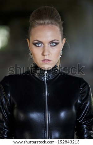 young woman in fetish leather catsuit and make-up - stock photo