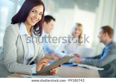 Young woman in foreground smiling at camera while her colleagues - stock photo