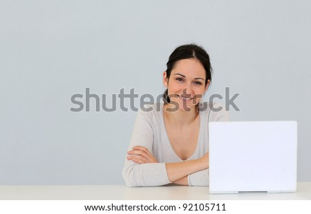 Young woman in front of laptop computer isolated - stock photo