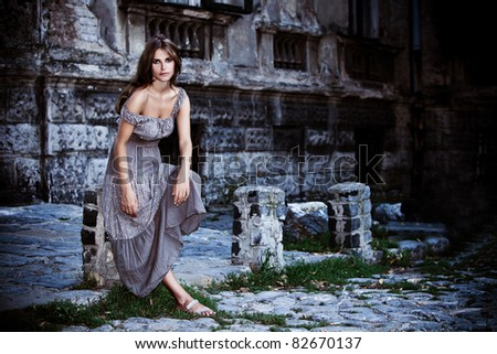 young woman in front of old stone house, outdoor portrait at dusk - stock photo