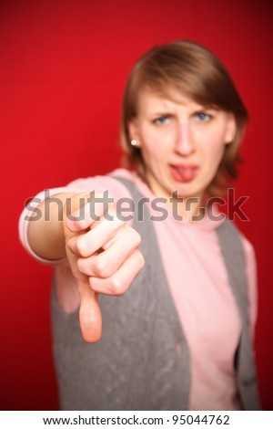 young woman in front of red background sticking out her tongue and pulling thumbs down expressing negativity (focus on hand) - stock photo