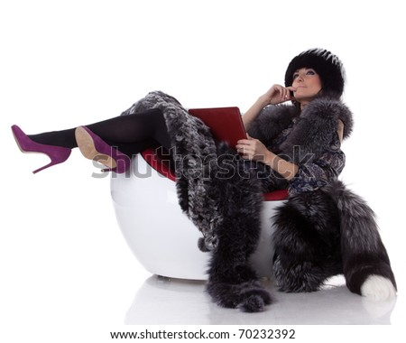Young woman in fur with laptop sit on armchair on a white background. - stock photo