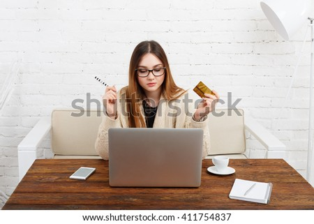 Young woman in glasses makes online shopping at home. Girl holds credit card looking at laptop. Sitting at pc with plastic card and shopping in modern white room. Online buying, e-commerce concept.   - stock photo