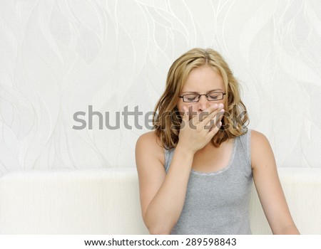 Young woman in glasses yawning - stock photo