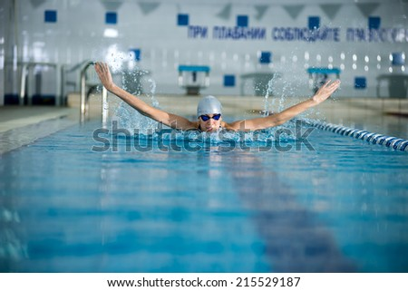 Young woman in goggles and cap swimming butterfly stroke style in the blue water indoor race pool - stock photo