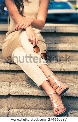young woman in golden pants and sandals sit on stairs with sunglasses in hand, outdoor shot - stock photo
