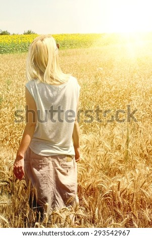 Young woman in golden wheat, sunlight, enjoy  - stock photo