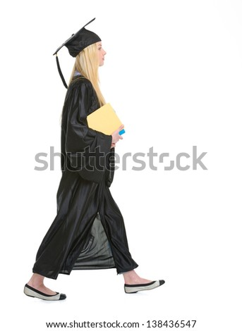 Young woman in graduation gown with books going sideways - stock photo