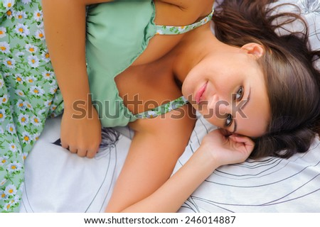 Young woman in green dress rest in the grass - stock photo