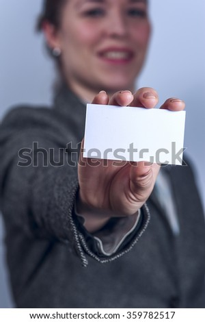 Young woman in grey suit holds business card - stock photo