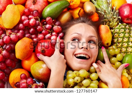 Young woman in group of fruit. Healthcare. - stock photo