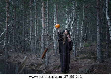 Young woman in Halloween witch costume in the autumn forest with yellow pumpkin. toning photo - stock photo
