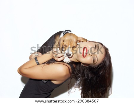 Young woman in happines emotions huging puppy against white wall - stock photo