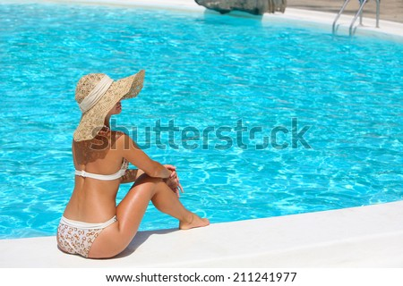Young woman in hat sitting on the ledge of the pool.  - stock photo