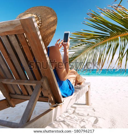 Young woman in hat with mobile phone at the beach - stock photo