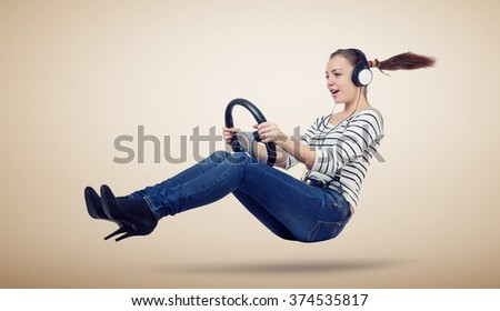Young woman in headphones driver car with a wheel, auto concept - stock photo