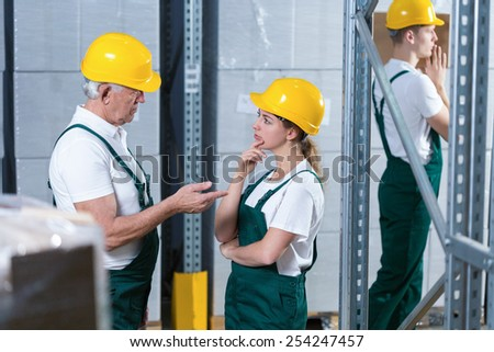 Young woman in helmet talking to her older supervisor - stock photo