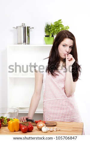 young woman in her kitchen chopping vegetables sucking her thumb - stock photo