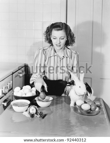 Young woman in her kitchen coloring Easter eggs - stock photo
