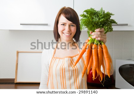 Young woman in her kitchen holding a bundle of carrots - stock photo