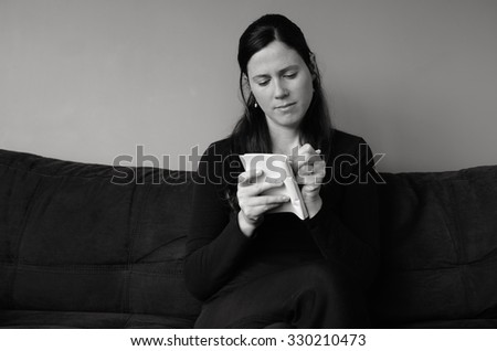 Young woman in her thirties (30s) writing on notepad to do list at home  (BW) - stock photo