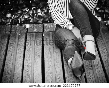 Young woman in high heel shoes and with red manicure sitting on Love locks bridge in Paris. Retro aged photo. Black and white. Shadowed angles. - stock photo