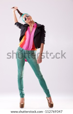 young woman in high heels and leather jacket pulling her hair - stock photo