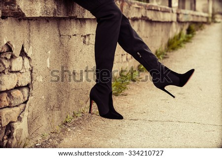 young woman in  high heels boots,  outdoor on street, closeup - stock photo