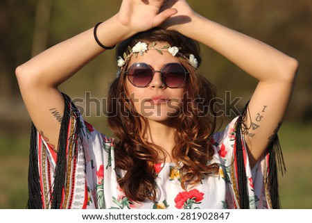 Young woman in hippie style looking at the camera and holding hands on heads - stock photo