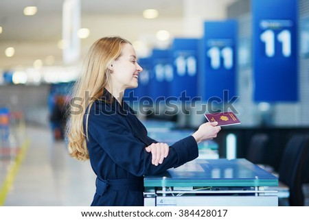 Young woman in international airport at check-in counter, giving her passport to an officer and waiting for her boarding pass - stock photo