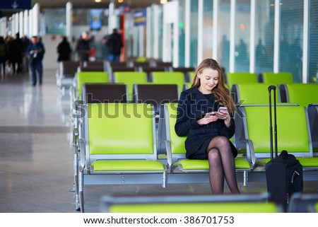 Young woman in international airport, checking her phone while waiting for her flight - stock photo