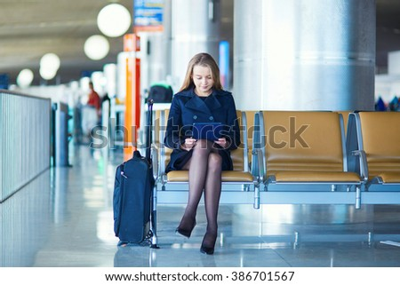 Young woman in international airport, waiting for her flight, using her tablet - stock photo