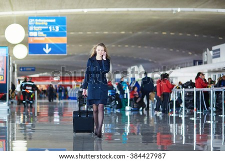 Young woman in international airport, walking with her luggage and speaking on the phone - stock photo