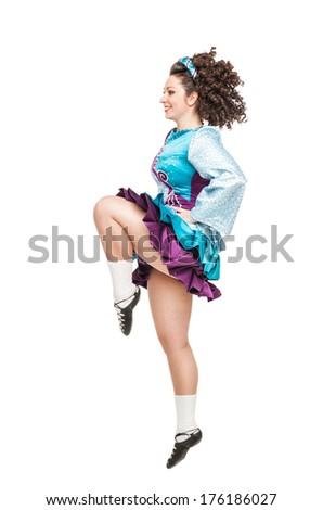 Young woman in irish dance dress dancing isolated - stock photo