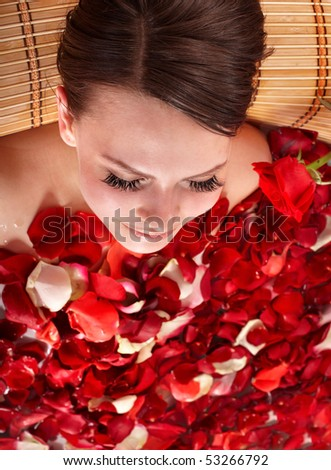 Young woman in jacuzzi with rose petal. - stock photo