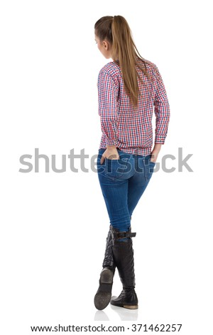 Young woman in jeans, black boots and lumberjack shirt standing with hands in back pocket. Rear view. Full length studio shot isolated on white. - stock photo
