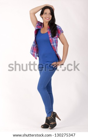 Young woman in jeans in the 50 s-chic in the office and checked blouse with blue top / Style News - stock photo