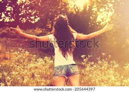 young woman in jeans shorts and t -shirt from back enjoy in summer day with arms open,  retro colors,  sun flare - stock photo