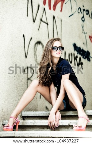 young woman in jeans shorts wearing sunglasses sit on stairs in front of graffiti city wall - stock photo