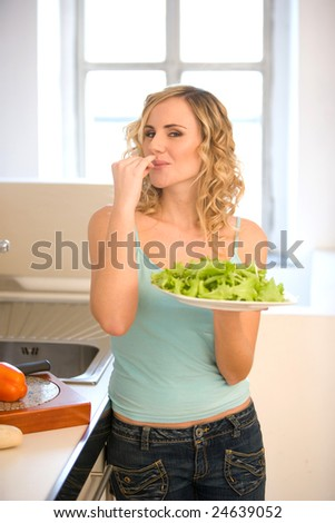 young woman in kitchen eating salad - stock photo