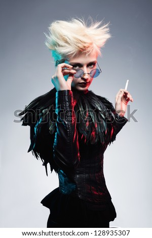 young woman in leather clothes holding her glasses and looking at camera while holding a cigarette in her other hand - stock photo