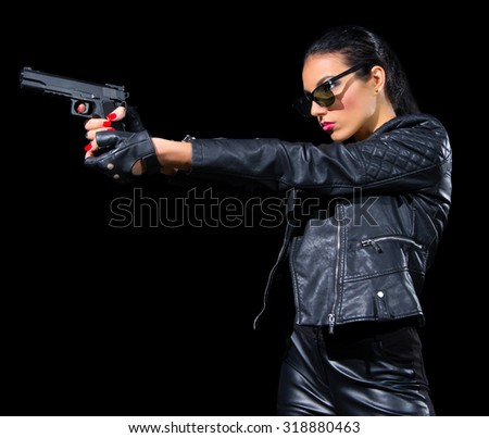 Young woman in leather clothes with gun isolated - stock photo