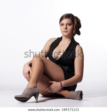 Young woman in leather jacket, miniskirt, high heels, with exceptional hairstyle sitting on the floor - stock photo
