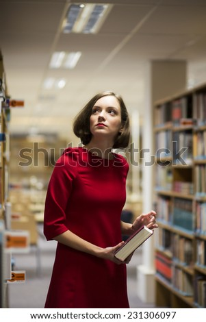 Young woman in library between shelves with book - stock photo